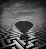 Overcome Obstacles Concept. As a hot air balloon cast shadow on a maze or labyrinth as a motivational business metaphor for rising above challenges Royalty Free Stock Image
