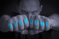 OVERCOME written on an angry man's fists. OVERCOME written on the fingers of an angry man's fists. Gray colored. Message concept image royalty free stock photo