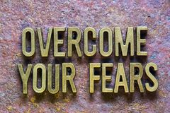 Overcome your fears. Phrase made from metallic letters over rusty metallic background Royalty Free Stock Photography
