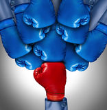 Overcoming Adversity. And conquering challenges as a group of blue boxing gloves ganging up on a single red glove as a business symbol of difficult competition Royalty Free Stock Photos