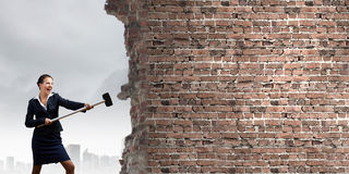 Overcoming challenges. Young attractive businesswoman with hammer in hands Stock Images