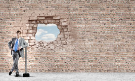 Overcoming challenges. Young businessman with big hammer against wall stock photo
