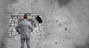 Overcoming challenges. Young businessman with big hammer against wall stock image