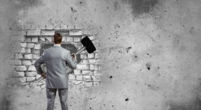 Overcoming challenges. Young businessman with big hammer against wall stock images