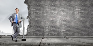 Overcoming challenges. Young businessman with big hammer against wall royalty free stock photography