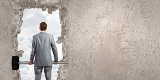 Overcoming challenges. Young businessman with big hammer against wall stock photos