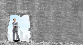Overcoming challenges. Young businessman with big hammer against wall royalty free stock photos