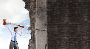 Overcoming challenges. Young businessman breaking cement wall with axe stock photography