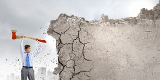Overcoming challenges. Young businessman breaking cement wall with axe royalty free stock photography
