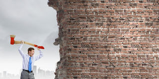 Overcoming challenges. Young businessman breaking cement wall with axe royalty free stock photos