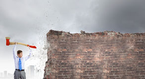 Overcoming challenges. Young businessman breaking cement wall with axe stock image