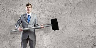 Overcoming challenges. Young businessman breaking cement wall with hammer royalty free stock photos