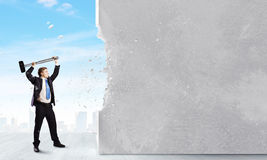 Overcoming challenges. Young businessman breaking cement wall with hammer stock photography