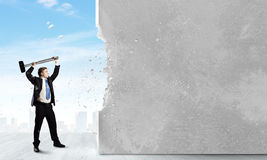 Overcoming challenges. Young businessman breaking cement wall with hammer stock photo