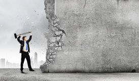 Overcoming challenges. Young businessman breaking cement wall with hammer royalty free stock image