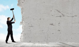 Overcoming challenges. Young businessman breaking cement wall with hammer royalty free stock photo