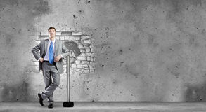 Overcoming challenges. Young businessman breaking cement wall with hammer stock images