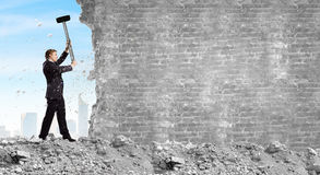Overcoming challenges. Young businessman breaking cement wall with hammer royalty free stock photography