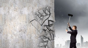 Overcoming challenges. Young businessman breaking cement wall with hammer Stock Photos