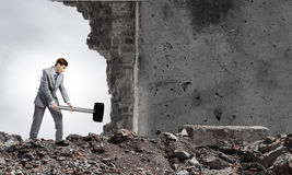 Overcoming challenges. Young businessman breaking old wall with hammer stock images