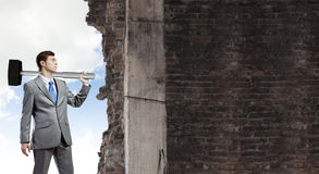 Overcoming challenges. Young businessman breaking old wall with hammer stock photos