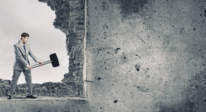 Overcoming challenges. Young businessman breaking old wall with hammer royalty free stock images