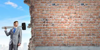 Overcoming challenges. Young businessman breaking old wall with hammer royalty free stock photo