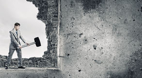 Overcoming challenges. Young businessman breaking old wall with hammer stock photography