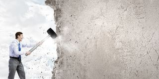 Overcoming challenges. Young businessman breaking old wall with hammer royalty free stock photos