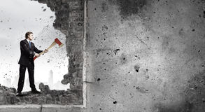 Overcoming challenges. Young determined businessman crashing wall with axe stock photography