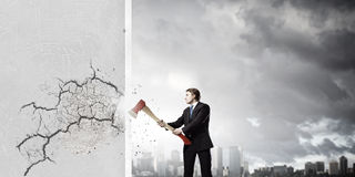 Overcoming challenges. Young determined businessman crashing wall with axe royalty free stock images