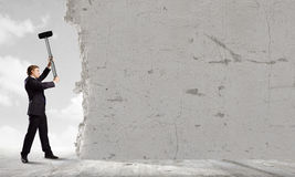 Overcoming challenges. Young determined businessman crashing wall with hammer royalty free stock image