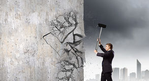 Overcoming challenges. Young determined businessman crashing wall with hammer royalty free stock photography