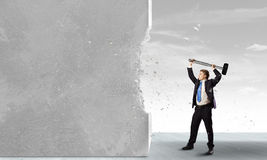 Overcoming challenges. Young determined businessman crashing wall with hammer stock photo