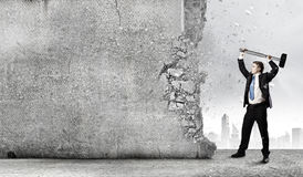 Overcoming challenges. Young determined businessman crashing wall with hammer royalty free stock images