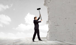 Overcoming challenges. Young determined businessman crashing wall with hammer royalty free stock photo