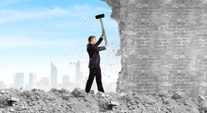 Overcoming challenges. Young determined businessman crashing wall with hammer royalty free stock photos