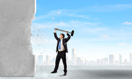 Overcoming challenges. Young determined businessman crashing wall with hammer stock photography