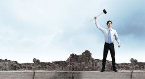 Overcoming challenges. Young determined businessman with hammer in hands Royalty Free Stock Photo