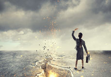 Overcoming crisis break. Young businesswoman outdoor at cracked asphalt road. Mixed media Stock Photo