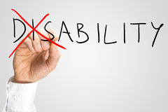 Overcoming a disability. Concept with a man writing the word Disability on a virtual interface and then crossing through the - Dis - with a red marker pen as a Stock Image