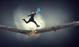 Overcoming fear of failure . Mixed media. Businessman running on broken wooden log above gap stock photo