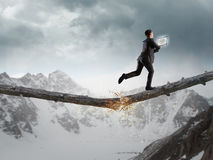 Overcoming fear of failure . Mixed media. Businessman running on broken wooden log above gap royalty free stock photos