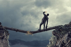 Overcoming fear of failure . Mixed media. Businessman running on broken wooden log above gap royalty free stock image
