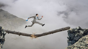 Overcoming fear of failure . Mixed media. Businessman running on broken wooden log above gap royalty free stock photography
