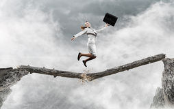 Overcoming fear of failure . Mixed media. Businesswoman jumping on broken wooden log above gap royalty free stock photography