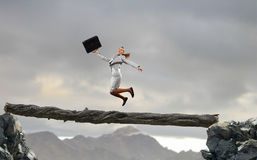 Overcoming fear of failure . Mixed media. Businesswoman jumping on broken wooden log above gap. Mixed media stock photo