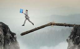 Overcoming fear of failure . Mixed media . Mixed media. Businessman running on broken wooden log above gap. Mixed media stock photography