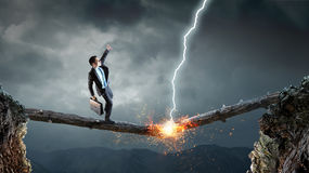Overcoming fear of failure . Mixed media . Mixed media. Businessman running on broken wooden log above gap. Mixed media royalty free stock photo