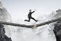 Overcoming fear of failure . Mixed media . Mixed media. Businessman running on broken wooden log above gap. Mixed media royalty free stock photos